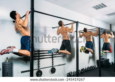 Group of Muscular Men Doing Pull Ups as part of Crossfit Training - stock photo