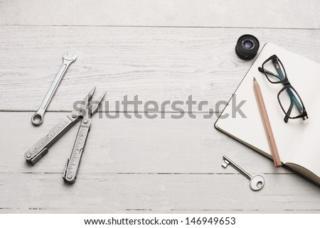 Group of object and a plain textbook on white hardwood table, Copy space. Studio shot. - stock photo