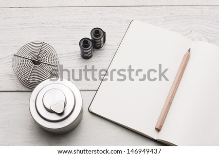 Group of objects on white hardwood table. Blank textbook and copy space. Studio shot - stock photo