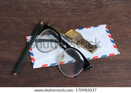 Group of objects on wooden desk. Glasses, watch, envelope and pencil  , Studio shot. - stock photo
