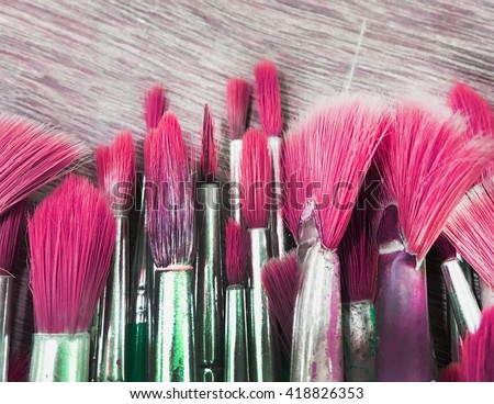 Group of old paint blushes on wooden in pink tone - stock photo
