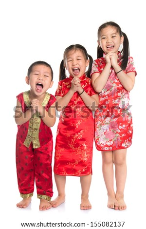 Group of oriental children wishing you a happy Chinese New Year, with traditional Cheongsam full length standing isolated on white background. - stock photo