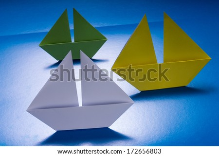Group of Paper Boats Sailing on Blue paper sea. Origami Ship - stock photo