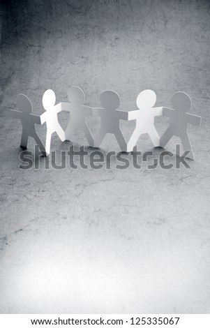 Group of paper chain people holding hands together. - stock photo