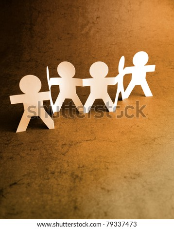 Group of paper doll people holding hands. Teamwork idea - stock photo