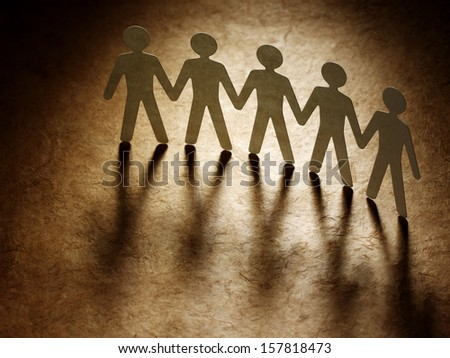 Group of paper people holding hands. Teamwork concept - stock photo