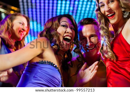 Group of party people - a man and women - dancing in a disco club to the music - stock photo