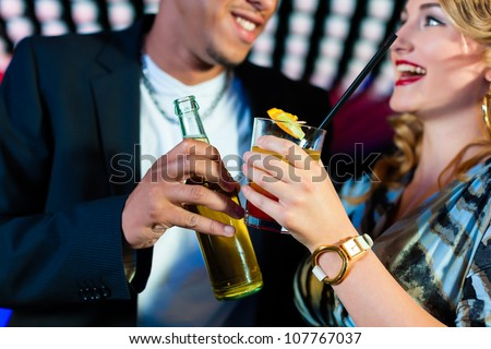 Group of party people - here a couple - with cocktails and beer in a bar or club having fun - stock photo