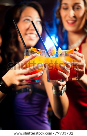 Group of party people - two friends - with cocktails in a bar or club having fun - stock photo