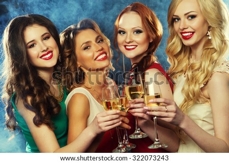 Group of partying girls clinking flutes with sparkling wine - stock photo
