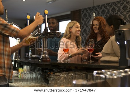 Group of people at a pub, enjoying drinks and talking. A bartender can be seen pouring a pint. - stock photo