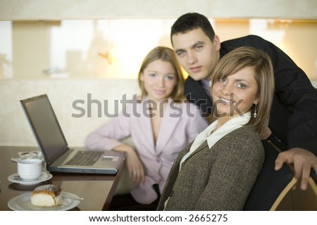 Group of People at the Cofe Table with Laptop. Short Depth of Focus (On First Person's Face). - stock photo