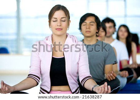group of people at the gym doing yoga and meditation exercises - stock photo