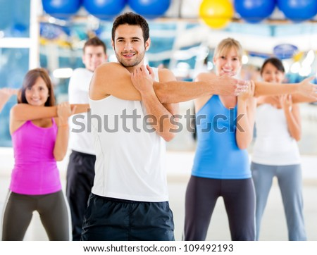 Group of people at the gym stretching to warmup - stock photo