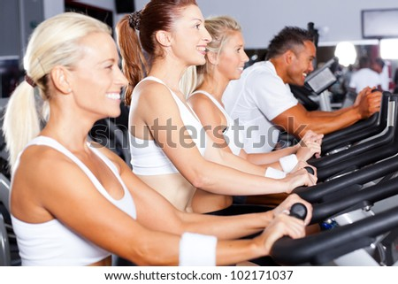 group of people cycling in gym - stock photo