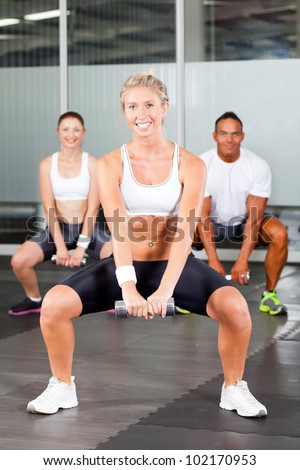 group of people doing fitness exercise with dumbbell in gym - stock photo