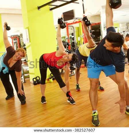 Group of people doing fitness workout in health club. - stock photo