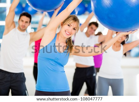 Group of people doing Pilates with a Swiss ball - stock photo