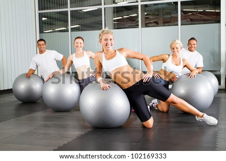 group of people doing workout with gymnastic ball in a gym - stock photo