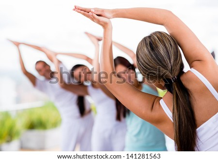 Group of people doing yoga and stretching - stock photo