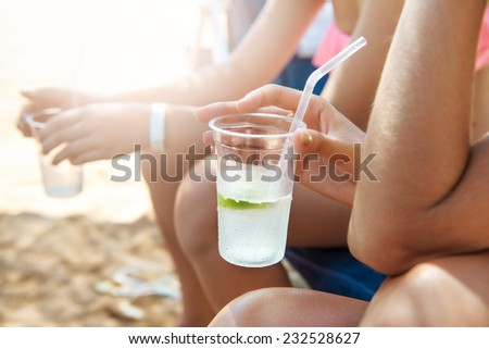 Group of people drinking cocktails on the beach - stock photo