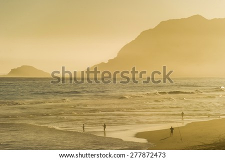 Group of people fishing during sunset. - stock photo