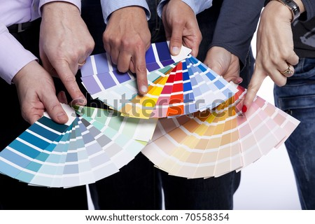 Group of people hands pointing to color samples in palette pantone (selective focus) - stock photo