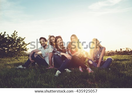 Group of people having fun outdoors; sunset  - stock photo