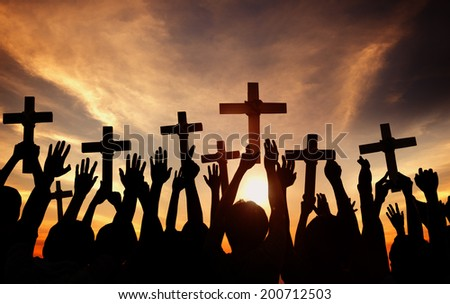 Group of People Holding Cross and Praying in Back Lit - stock photo