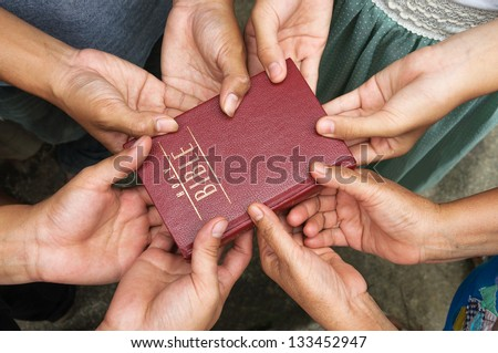 Group of people holding Holy Bible and praying. - stock photo