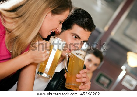 Group of people in a bar or restaurant drinking beer, one couple flirting very obviously having a lot of fun - stock photo