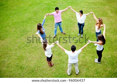Group of people in a circle holding hands - outdoors - stock photo