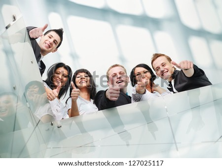 Group of people inside the modern building with thumbs up - stock photo