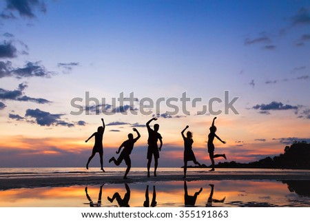 group of people jumping on the beach at sunset, silhouette of friends having fun together - stock photo