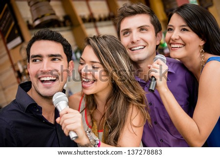 Group of people karaoke singing at a bar having fun - stock photo