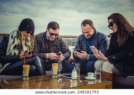 Group of people looking at a cell phone and laughing - stock photo