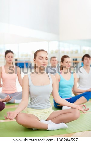 Group of people meditating in lotus position - stock photo