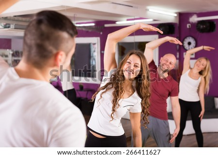 Group of people men and women limbering up in a gym - stock photo