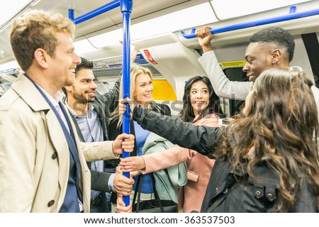 Group of people on tube train in London. They are a mixed group of persons, wearing smart casual clothes. They could be friends or just strangers. Urban lifestyle and transportation concepts. - stock photo