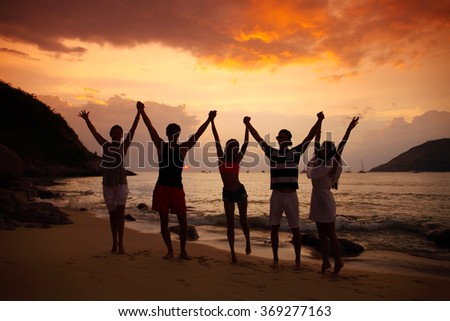 Group of people partying on beach at sunset - stock photo
