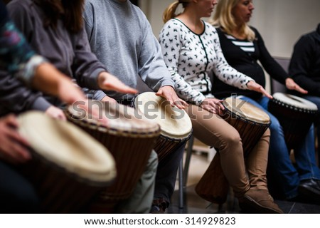 Group of people playing on drums - therapy by music - stock photo