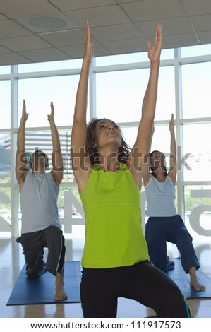 Group of people practicing yoga with raised arms - stock photo