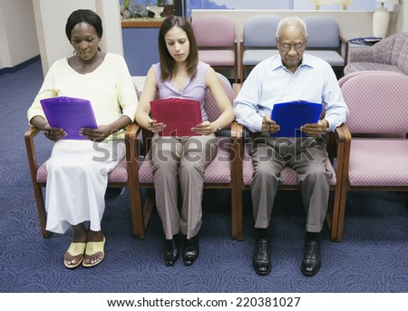 Group of people reading paperwork while sitting in waiting room - stock photo