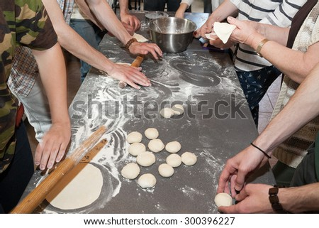 Group of people rolling dough on table with flour - stock photo