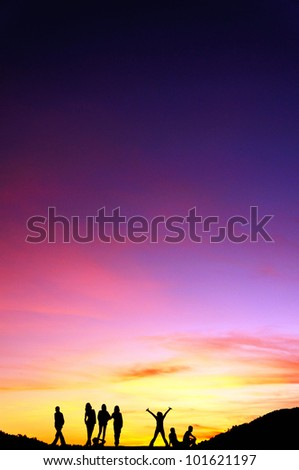 group of people's silhouette on the jetty isolated over sunset and dramatic sky - stock photo