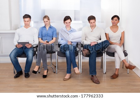 Group Of People Sitting On Chair In A Waiting Room - stock photo