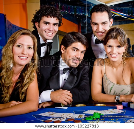 Group of people smiling playing roulette at the casino - stock photo