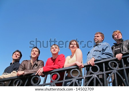 group of people stand leaning on handrail - stock photo