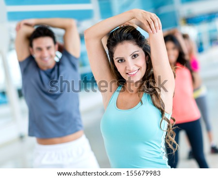 Group of people stretching at the gym and smiling  - stock photo