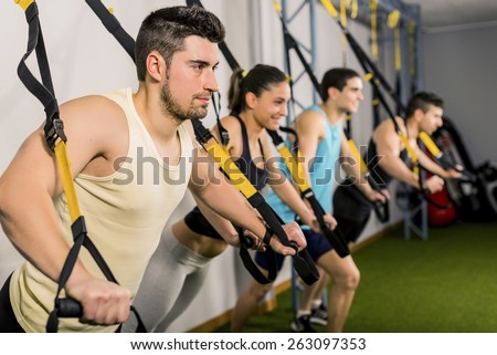 Group of people training at elastic rope in gym - stock photo